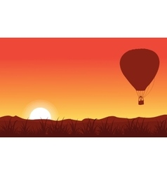 Silhouette of hot air balloon on orange sky vector