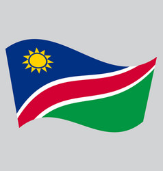 Flag of namibia waving on gray background vector