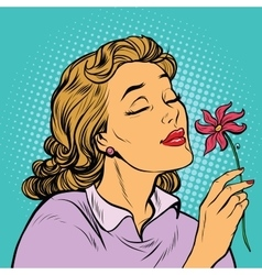Beautiful woman inhaling fragrance of a flower vector