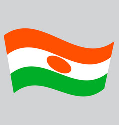 Flag of niger waving on gray background vector