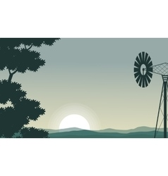 Silhouette of windmill and tree on the morning vector
