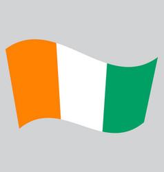 Flag of ivory coast waving on gray background vector