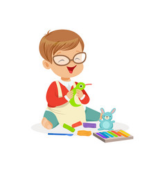 Cute little boy making figures from a plasticine vector