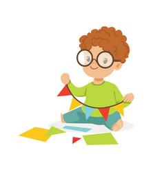 Cute little boy making a garland of pennants kids vector