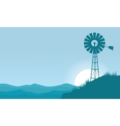 Silhouette of windmill on the hill scenery vector