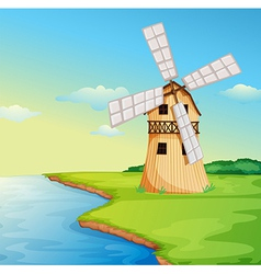 A windmill along the river vector