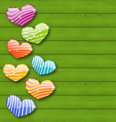 Multicolored striped hearts on green wooden vector image vector image