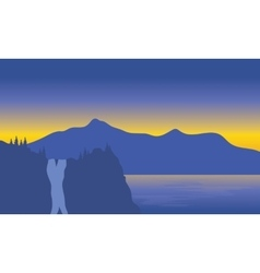 Silhouette of waterfall beside the sea vector