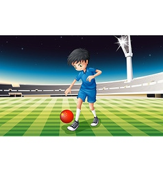 A boy playing soccer at the field vector image