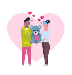 cute couple holding teddy bear toy over heart vector image