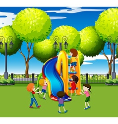 Kids playing on slide in the park vector image vector image