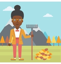 Woman with rake standing near heap of autumn vector