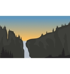Silhouette of waterfall at sunset vector