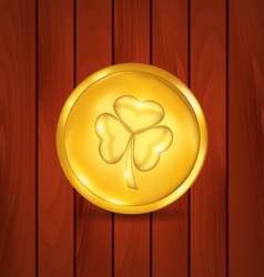 Golden coin with clover on brown wooden texture vector