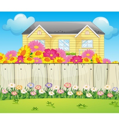 A house surrounded with colorful flowers vector