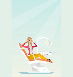 Afraid woman sitting in the dental chair vector