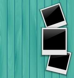 Three blank photo frames on wooden background vector