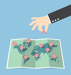 Businessman hand pin target to world map vector image