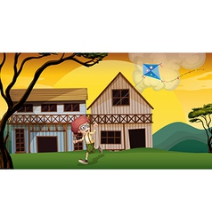 A boy playing with his kite in front of the wooden vector