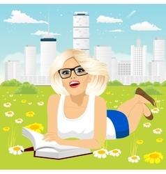 Woman lying down on grass reading book vector