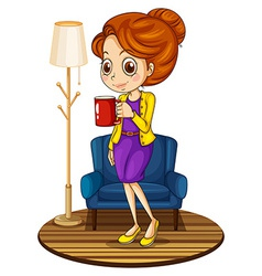 A woman near the blue couch holding a red mug vector
