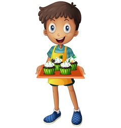 A young boy holding a tray with cupcakes vector