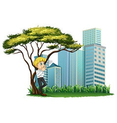 A man smoking under the tree across the buildings vector