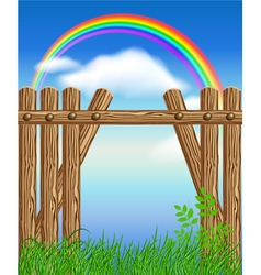 Wooden fence on green grass with rainbow vector image