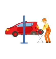 Smiling mechanic changing a tire in the garage vector