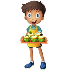 A young man holding a tray with cupcakes vector
