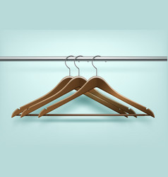 Clothes brown wooden hangers on background vector