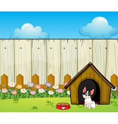 A puppy in front of the doghouse inside the fence vector image