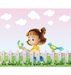A young girl playing with the birds near the fence vector image