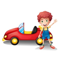 A young boy in front of a red car vector
