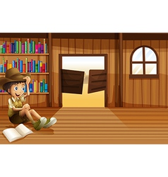 A young boy reading inside the room with a vector