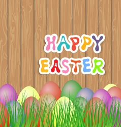 Easter eggs in the grass on a wooden background vector image