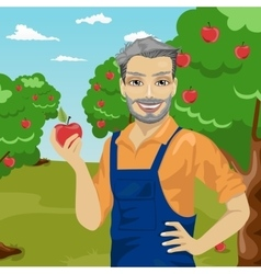 mature farmer man holding an apple in orchard vector image