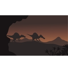 Silhouette of two spinosaurus walking in hills vector