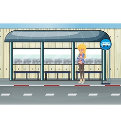 A girl standing at the waiting shed vector image