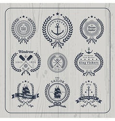 Vintage nautical wreath labels set on light wood vector
