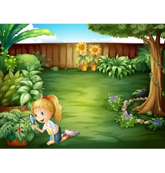 A girl studying the plants in the garden vector