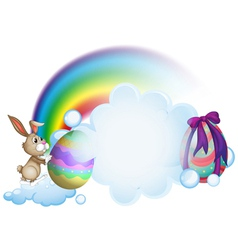 A bunny and the easter eggs near the rainbow vector image