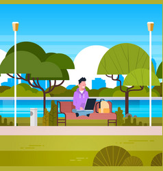 Young man sitting on bench in park using laptop vector