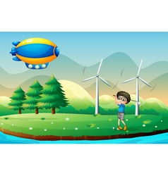 A boy playing golf in the field with windmills vector