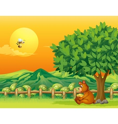 A bear sitting under a big tree vector image