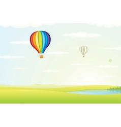 Hot air balloon over green fields image vector