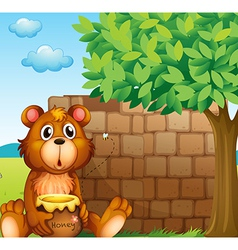 A bear with honey near a pile of bricks vector image