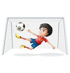 A boy playing soccer wearing a red uniform vector image