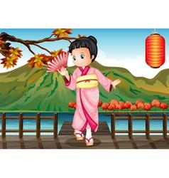A girl in a kimono attire at the bridge vector