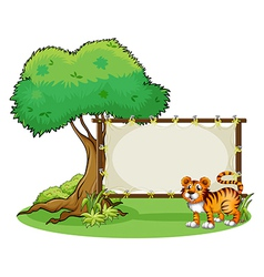 A tiger beside a wooden frame near a big tree vector image